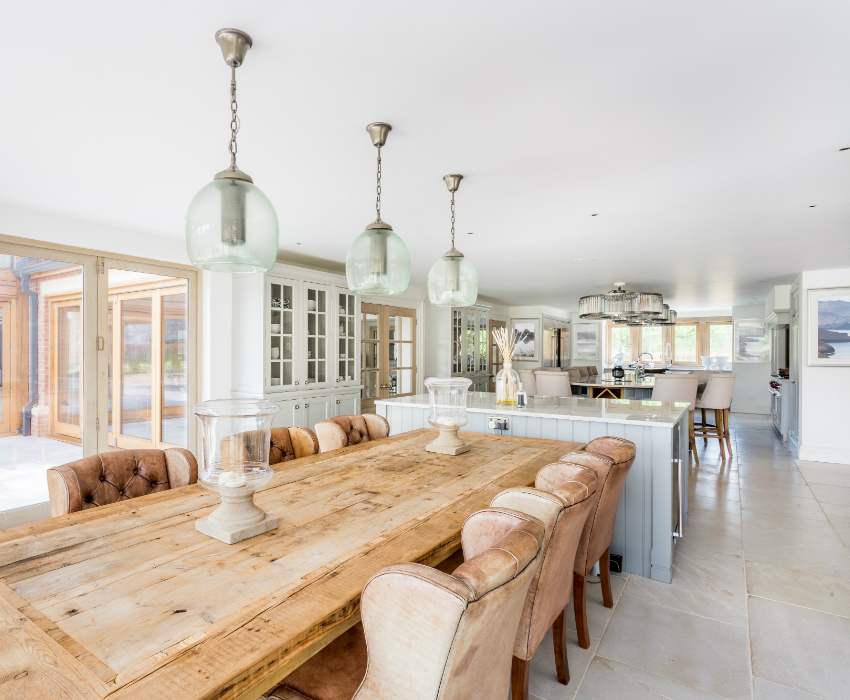 Open plan dining and kitchen with long wood table and Lulworth stone flooring