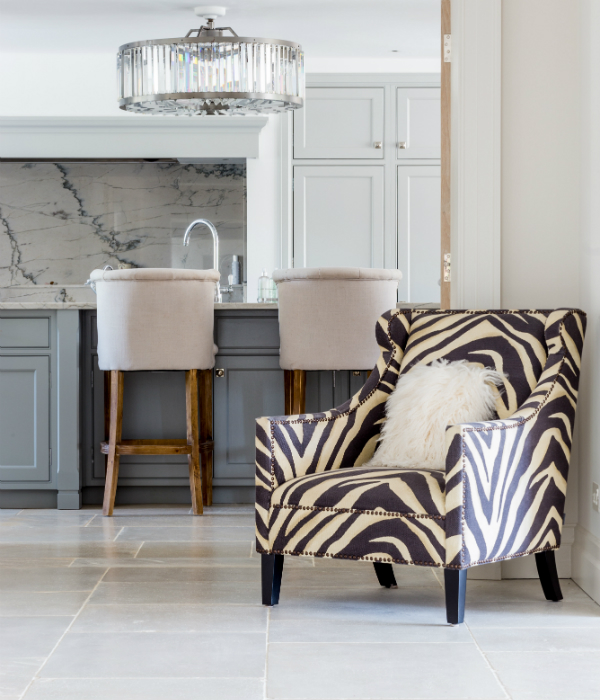 Interior shot of zebra pattern chair, fur cushion, and Lulworth stone flooring