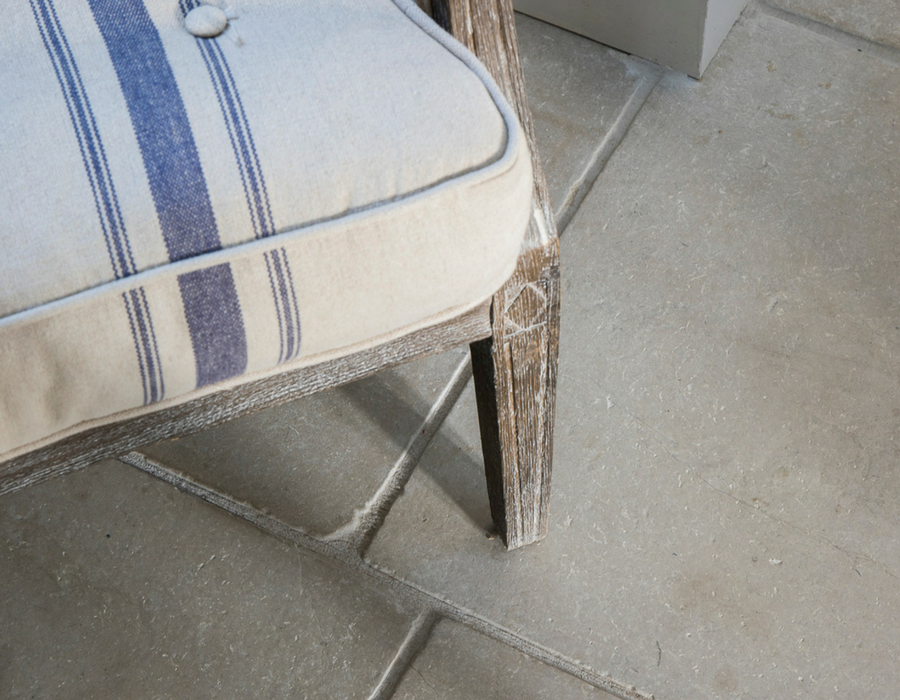 Striped arm chair in forefront with stone flooring behind